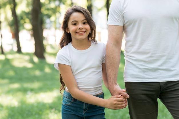 Muchacha bonita que mira la cámara que lleva a cabo la mano de su padre en parque