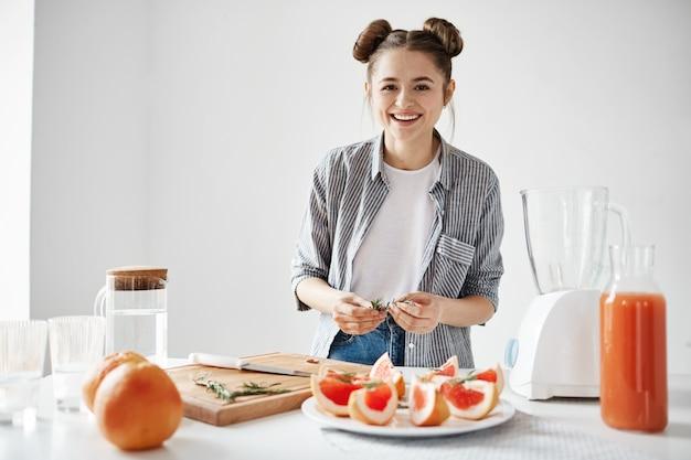 Muchacha bonita que sonríe la placa de decoración para el desayuno con el pomelo y el romero rebanados sobre la pared blanca. refrescante licuado de desintoxicación.