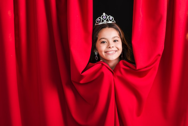 Muchacha bonita sonriente que lleva la corona que mira a escondidas de la cortina roja
