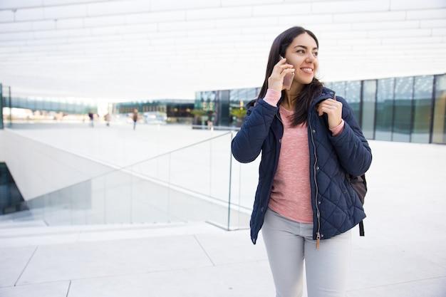 Muchacha bonita sonriente con la taleguilla usando el teléfono móvil al aire libre
