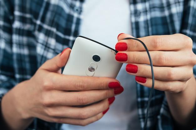 La muchacha en la camisa de tela escocesa que sostiene un teléfono elegante en sus manos con la manicura roja y conecta los auriculares