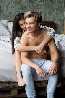 Muchacha cariñosa joven que abraza al hombre atractivo que se sienta en cama junto