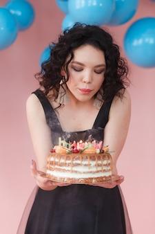 Muchacha caucásica bautiful que sopla velas en la torta de cumpleaños. globos azules en el fondo.
