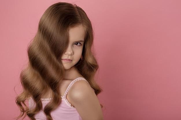 Muchacha caucásica hermosa con el pelo rojo brillante. pelo rizado de color rojo.