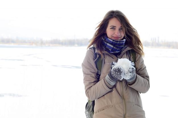 Una muchacha caucásica joven y alegre en una capa marrón en la nieve