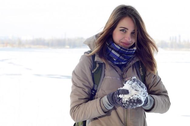 Una muchacha caucásica joven y alegre en una capa marrón sostiene una bola de nieve