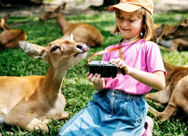 Muchacha caucásica joven que toma el selfie con los ciervos en el parque zoológico