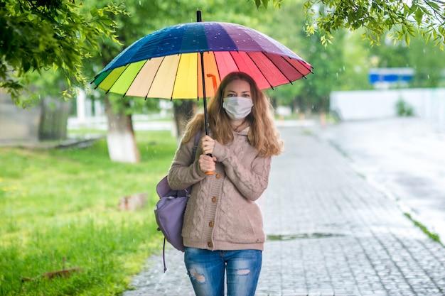 La muchacha caucásica en máscara protectora camina debajo de un paraguas en la calle vacía en lluvia de primavera. seguridad y distancia social