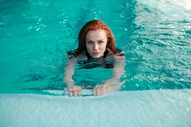 La muchacha caucásica del pelirrojo joven hermoso nada en la piscina de interior. estilo de vida saludable.