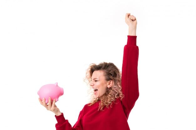 La muchacha caucásica con el pelo rubio rizado sostiene una hucha rosada del cerdo y ella es muy feliz, retrato aislado