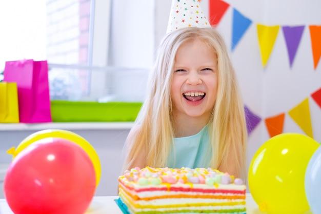 Muchacha caucásica rubia que se ríe de la cámara cerca de la torta del arco iris del cumpleaños. fondo colorido festivo con globos