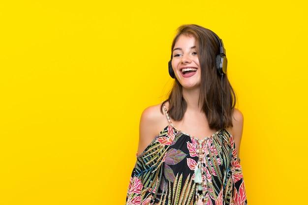 Muchacha caucásica en el vestido colorido aislado en amarillo que escucha la música con los auriculares
