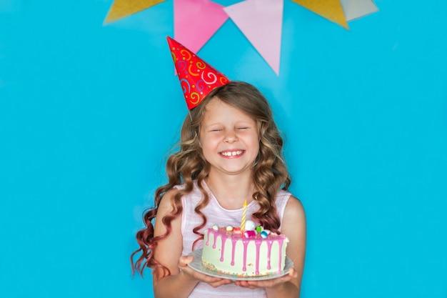 Muchacha de celebración joven que lleva a cabo un pedazo de torta en fondo azul. copia espacio