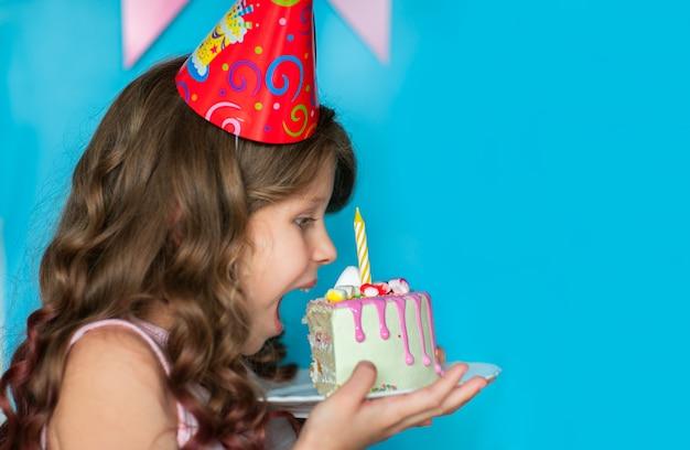Muchacha de celebración joven que muerde un pedazo de torta en fondo azul. copia espacio