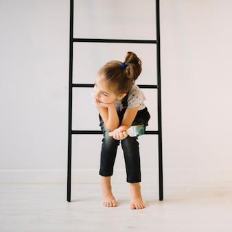 Muchacha con el cepillo que se sienta en escalera cerca de la pared en sitio