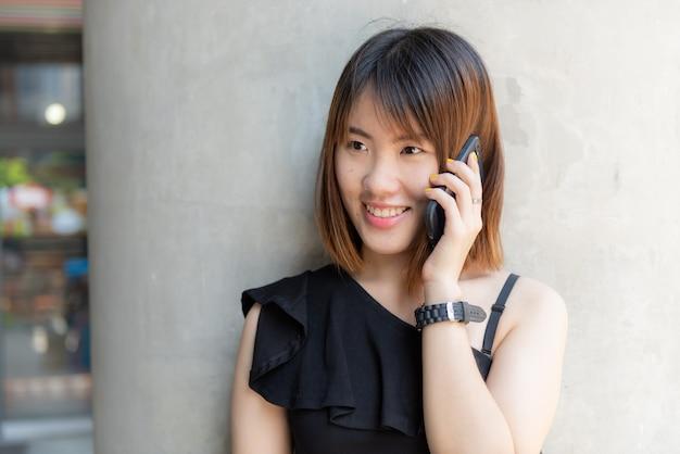 Muchacha china feliz del adolescente que habla el teléfono móvil con la cara sonriente