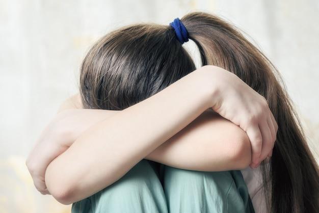 La muchacha con la coleta larga se sienta acurrucada apretando sus rodillas con sus manos. el concepto de abuso infantil.