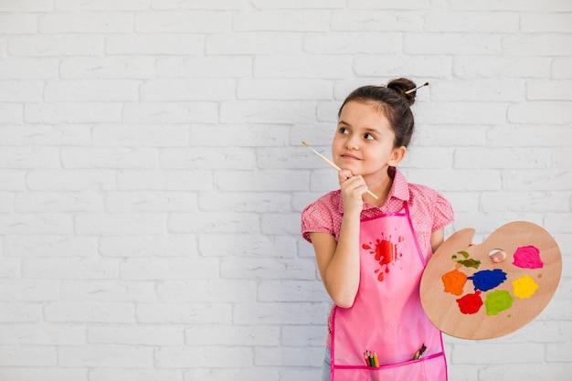 Muchacha contemplada que sostiene la paleta y la brocha en la mano que se coloca cerca de la pared blanca