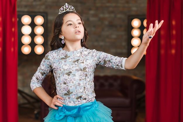 Muchacha con corona que se realiza en el escenario