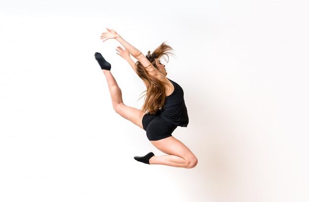 Muchacha de la danza joven sobre la pared blanca aislada