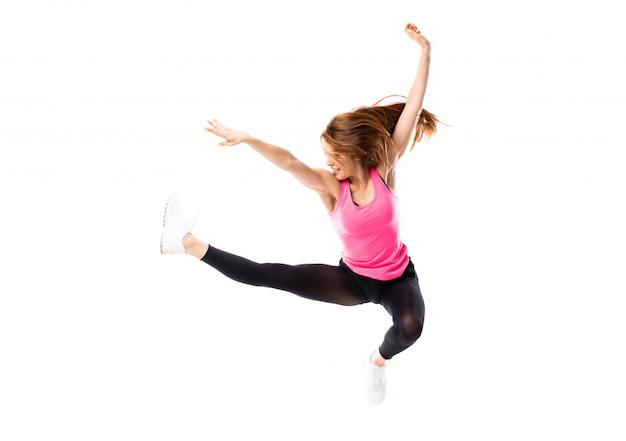 Muchacha de la danza joven sobre el salto blanco aislado del fondo