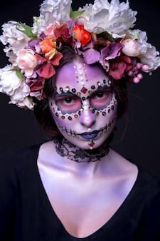 Muchacha de halloween con los rhinestones y la guirnalda de flores