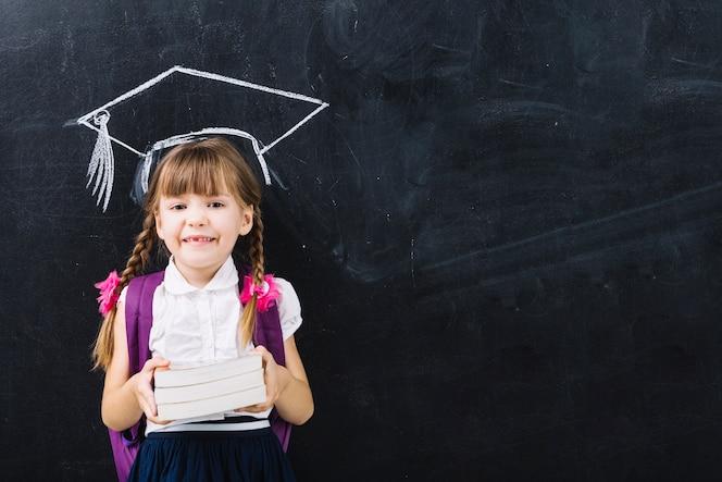 Muchacha del alumno con los libros en sombrero principal