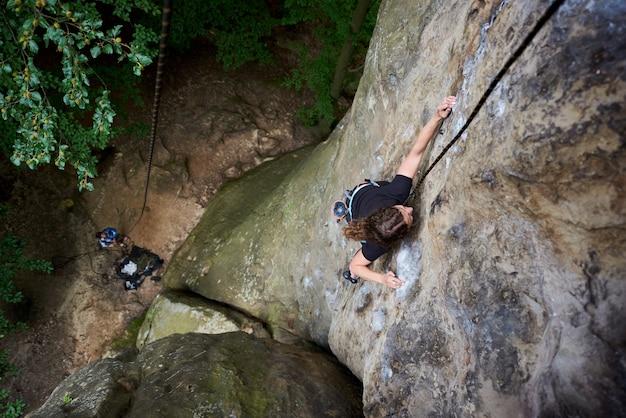 Muchacha delgada que supera la ruta de escalada difícil en rocas con la cuerda. verano extremo al aire libre. vista superior.