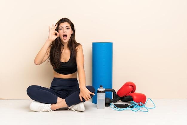 Muchacha del deporte del adolescente que se sienta en el piso sorprendida y que muestra la muestra aceptable