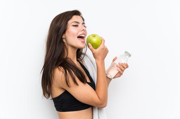Muchacha del deporte del adolescente sobre blanco aislado con una manzana y una botella de agua