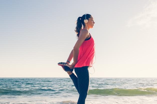 La muchacha del deporte en la playa en auriculares hace ejercicios de deportes en la mañana