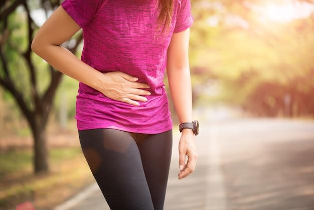 La muchacha del deporte tiene dolor de estómago después de trotar se resuelve en parque. concepto de salud