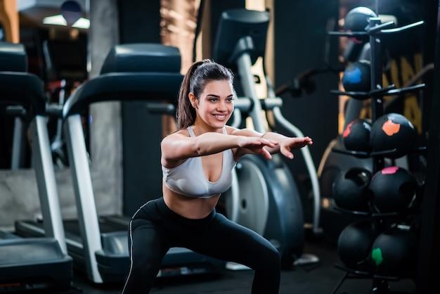 Muchacha deportiva hermosa que hace posiciones en cuclillas en el gimnasio.