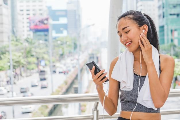Muchacha deportiva joven de la aptitud que corre y que escucha música en la ciudad