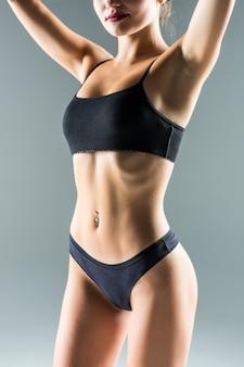 Muchacha deportiva de risa en bikini negro posando en la pared gris. foto de chica atractiva con cuerpo tonificado delgado. concepto de belleza y cuidado corporal