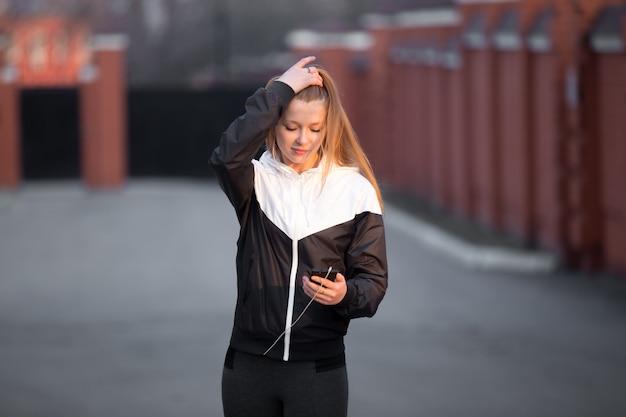 Muchacha deportiva con el teléfono celular