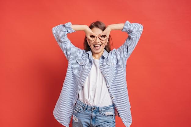 Muchacha divertida, linda que se divierte aislada en una pared roja mientras que hace las manos de los prismáticos.