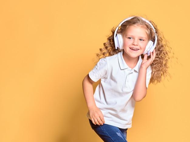 Muchacha divertida del niño pequeño en la camiseta blanca aislada en espacio amarillo. concepto de estilo de vida infantil. mock up copia espacio. escucha música en auriculares, baila con el cabello revoloteando