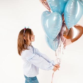 Muchacha divertida con orejas de gato con globos. cumpleaños de concepto