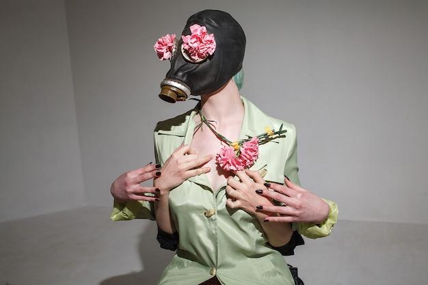 Muchacha divertida con el pelo verde con máscara de gas y una capa y sosteniendo flores de plástico rosa. la mano de alguien sosteniéndola por detrás. concepto loco gonzo juguetón