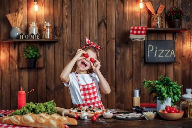 Muchacha divertida que cocina la pizza y que engaña con los tomates
