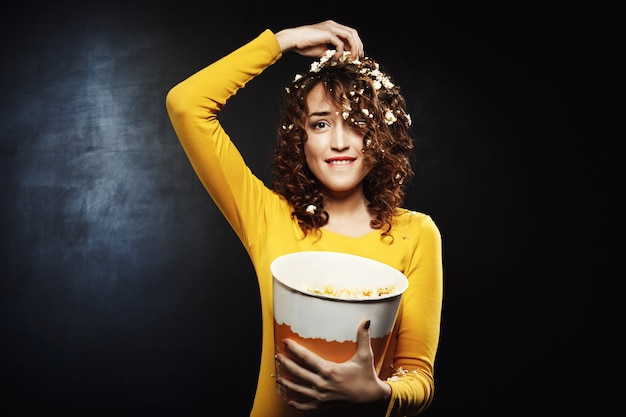 Muchacha divertida que come palomitas de maíz mientras ve programas en la fiesta en casa