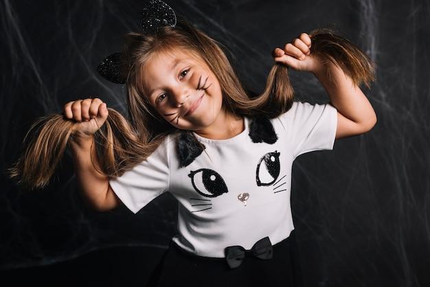Muchacha divertida en traje de gato tocando el cabello