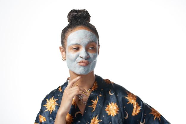 Muchacha divertida de yong con máscara de belleza de arcilla en modelo de piel aislada