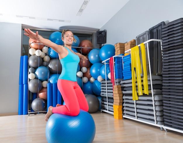 Muchacha en el ejercicio suizo del ejercicio del balance de la rodilla de la bola suiza del gimnasio