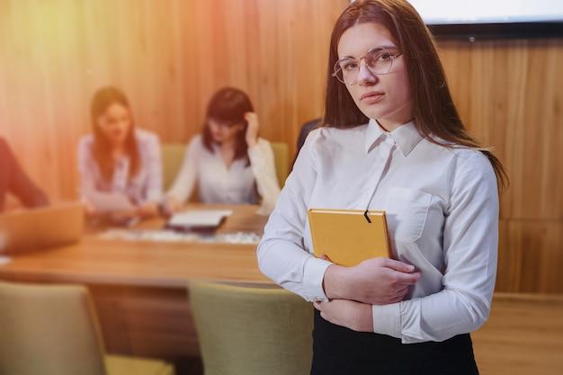 Muchacha elegante atractiva joven del oficinista en vidrios con un cuaderno en las manos en el fondo de colegas de trabajo