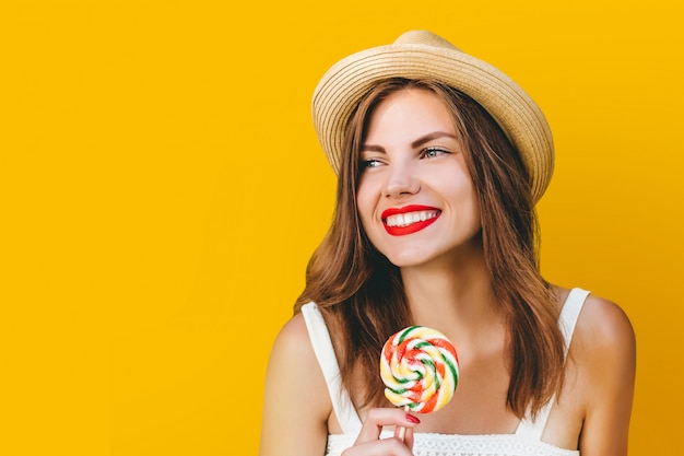 Muchacha elegante joven en un sombrero de paja con una piruleta del arco iris en un fondo amarillo
