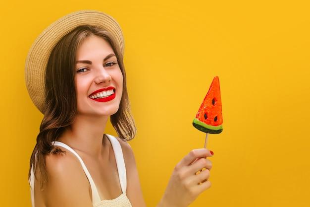 Muchacha elegante joven en un sombrero de paja con una piruleta multicolora en un fondo amarillo