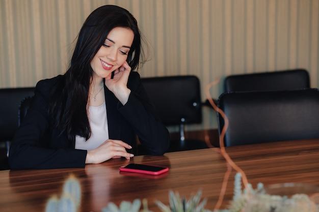 La muchacha emocional atractiva joven en el estilo del negocio viste sentarse en el escritorio con el teléfono en oficina o audiencia