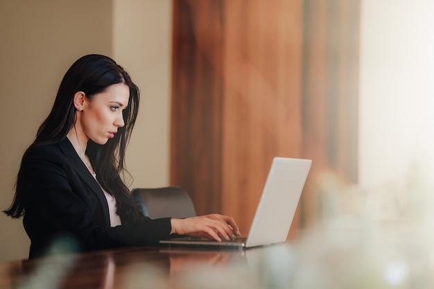 Muchacha emocional atractiva joven en la ropa del businessstyle que se sienta en un escritorio en un ordenador portátil y un teléfono en la oficina o el auditorio
